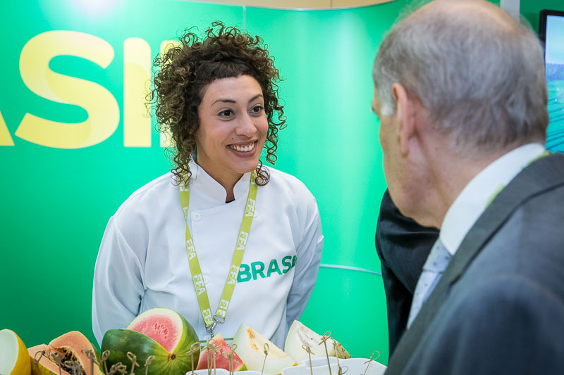 The fruit importer smiles while engaging her audience during an event for APEX Brasil in Brussels