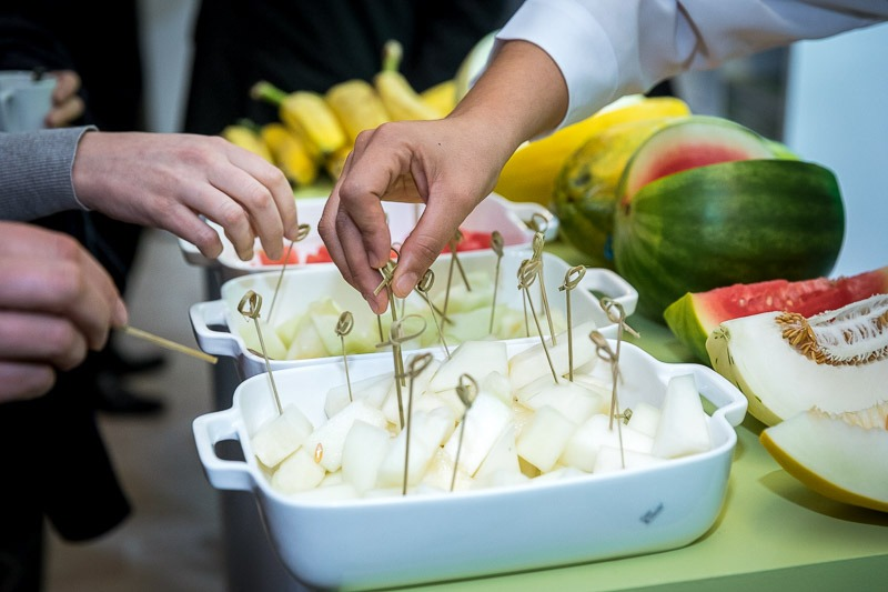 Hands approaching a fruit basket to try them during an event for APEX Brasil in Brussels
