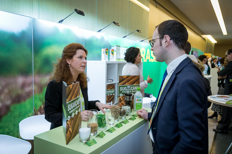 A sugar importer engages with a visitor at her kiosk during an event for APEX Brasil in Brussels