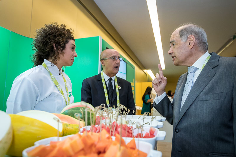 A visitor engaging the fruit importer at her stand during an event for APEX Brasil in Brussels