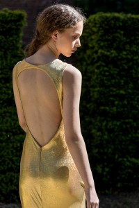 Fashion portrait of a girl with a golden dress seen from the back