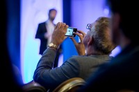 An attendee takes pictures with his cellphone during the CS International Conference 2018