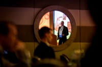 A speaker in seen through a mirror reflection during the CS International Conference 2018