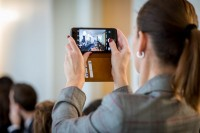 A woman takes a picture with her cellphone at the In4Wood Final Conference by EURADA, Brussels