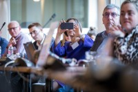 An attendee takes a picture with a cellphone at the In4Wood Final Conference by EURADA, Brussels