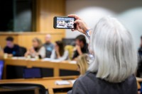 Attendee taking cellphone picture during the Breaking Point - Solving the European Wildlife Rescue Crisis Conference