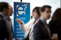 Banner of EURADA with blurred people during the EURADA General Assembly 2018