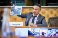Syed Hasnain, the Network for Refugee Voices, shows a picture during the MCE Conference at the EU Parliament