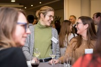 Two women speak and laugh during the Stellenbosch University cocktail at the South African Embassy, Brussels