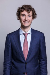 Corporate portrait of a young man wearing a blue suit with a pink tie
