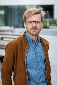 Portrait of a blond man wearing a blue shirt and brown jacket