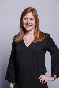 Corporate studio portrait of a ginger woman wearing a black dress smiling