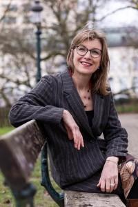 Portrait of Birgitta Bechtold sitting on a bench at Leopold Park, Brussels