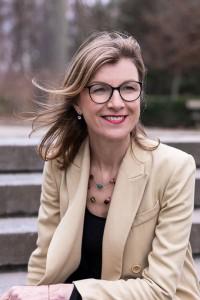 Portrait of Birgitta Bechtold wearing a light brown jacket at Leopold Park, Brussels